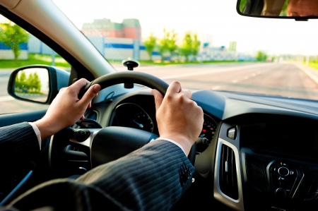 man holds the steering wheel firmly with both hands photo