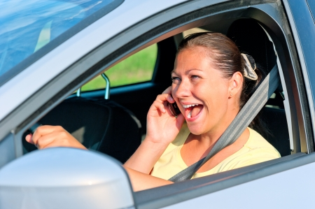 beautiful girl behind the wheel with phone laughing photo