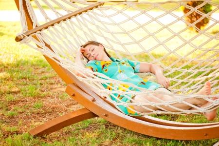girl in dress resting in a hammock photo