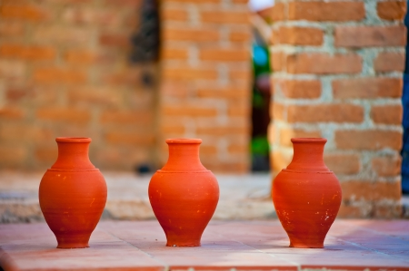 three handmade clay jug on brick wall background photo