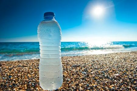 botella de agua fría en la playa de guijarros Foto de archivo