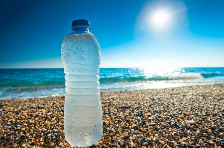 bottle of cold fresh water on the pebble beach