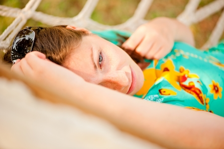 woman in a turquoise dress resting in a hammock  photo