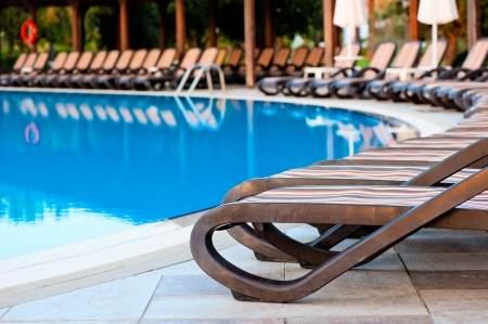 empty sun loungers for sunbathing and swimming pool photo