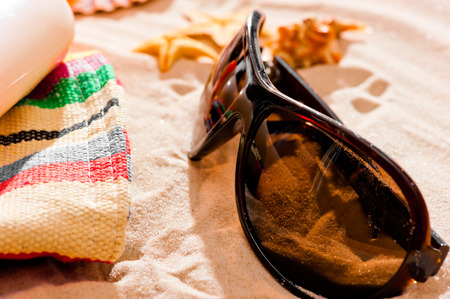 sunglasses and beach accessories on dry fine sand  photo