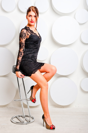 charming girl in a chair in lace dress photo