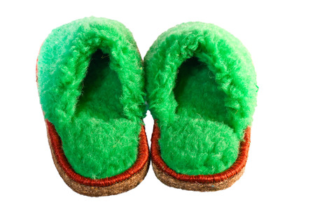 green slippers on a white background of wool sheep photo