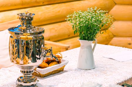 shiny samovar and bouquet of flowers on a rustic table photo