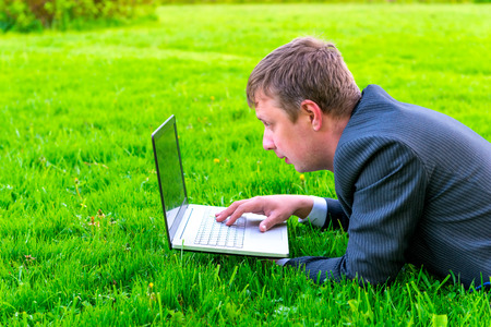 charming businessman lies on the grass with laptop photo