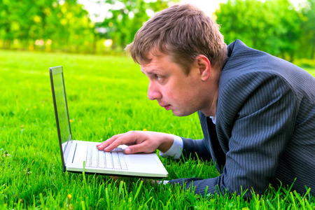 man working with a laptop lying on the lawn photo