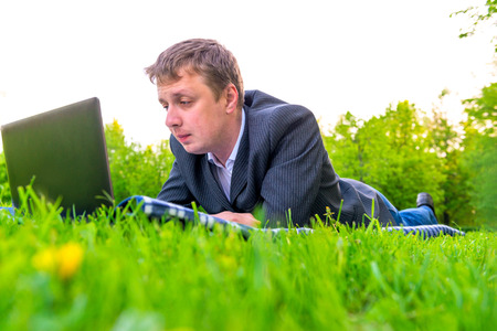 man working with laptop lying on the lawn photo