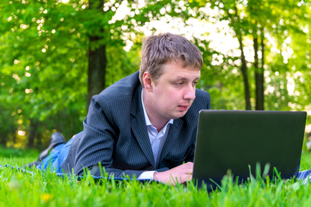 businessman intently working on a laptop on the grass photo