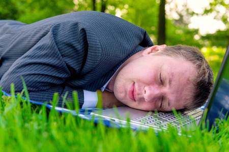 tired man asleep on a laptop in the park photo