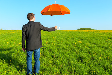 businessman offering an umbrella on a sunny day photo