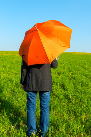 people under an orange umbrella in a field waiting for rain photo