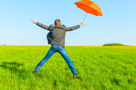 businessman with umbrella jumping in a field photo