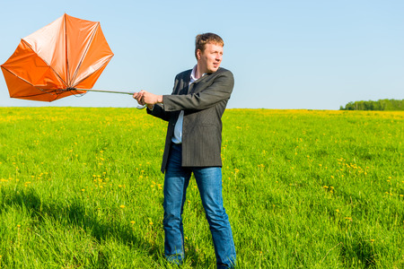strong wind wrenched orange umbrella man photo