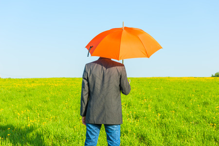 man under an umbrella on a sunny day in the field photo