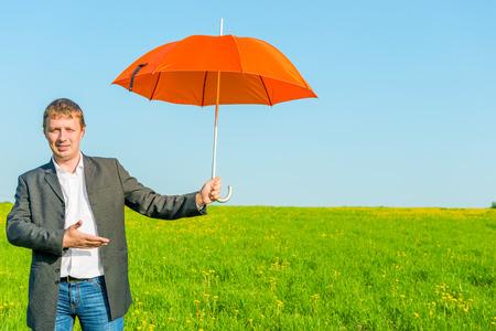 business man offers a sun umbrella in the field