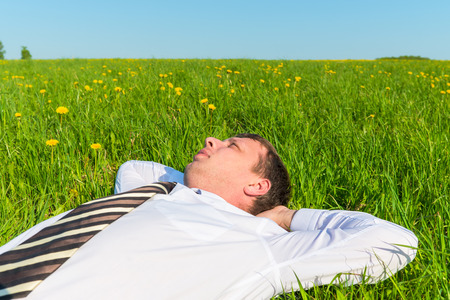 tired manager resting on green grass in field photo