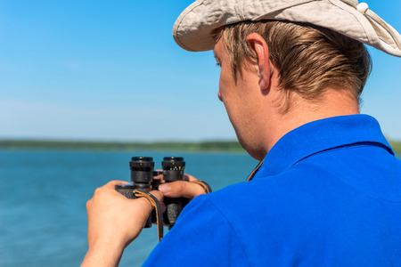 a young man with binoculars on the nature photo