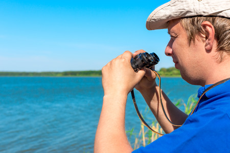 handsome young man with binoculars at lake photo