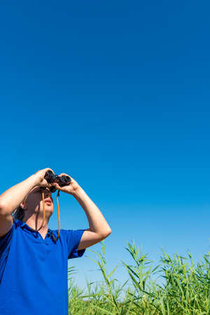 man looking through binoculars into the sky photo