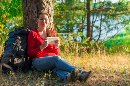 girl traveler resting in a tree with the tablet photo