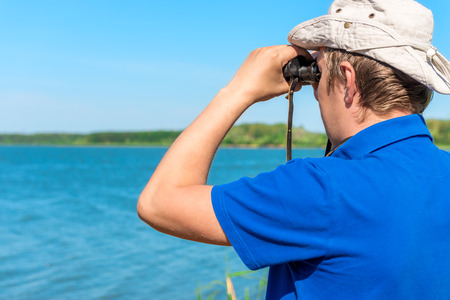 man with binoculars looks for something on the lake photo