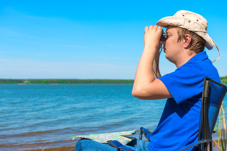 young man near the lake looking through binoculars photo