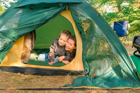 camping tent: mother and son in a tent on the nature