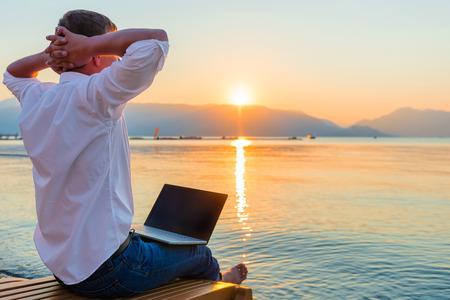 resor: Fritids entreprenör. Man med laptop på morgonen på stranden arbets Stockfoto