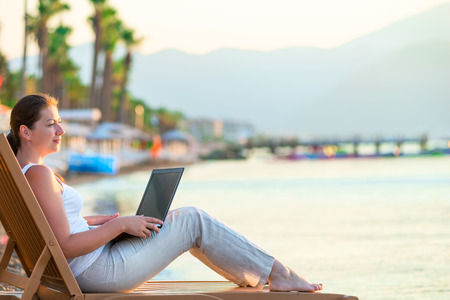 girl with a laptop looking at the sea in the morning photo