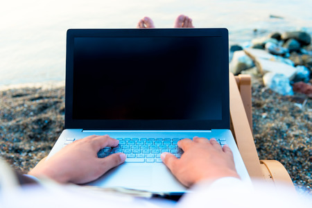 laptop on a man's lap near the sea