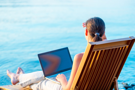 young carefree girl on a sun lounger with a laptop photo