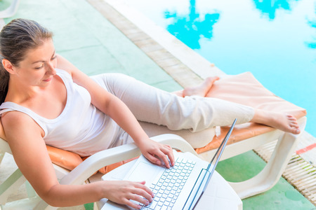 girl with a laptop in a lounge chair near the swimming pool photo