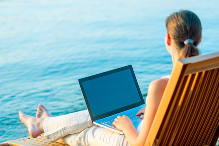 barefoot girl with a laptop on the beach working photo