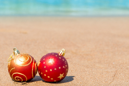 christmas tide: two red Christmas ball on the beach Stock Photo