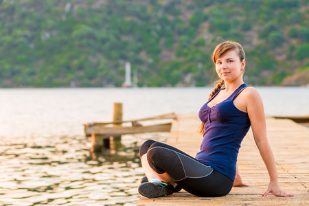 young brunette sitting on a pier in the lotus position photo