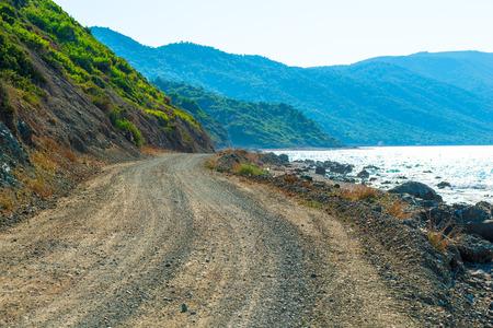 unpaved road: unpaved road runs along the sea