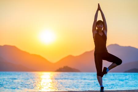 Pilates by the Sea. Girl balances at dawn photo