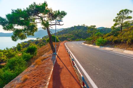 good asphalt road in the mountains near the sea Stock Photo
