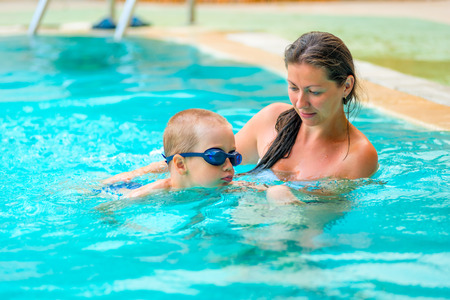 baby swimming: 5 years old boy learning to swim with mom