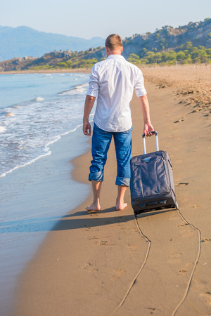 lost tourist with a suitcase on a desert island photo