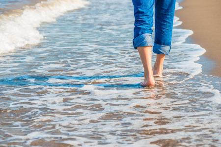 pies masculinos: piernas masculinas en jeans caminando por la orilla del mar de arena