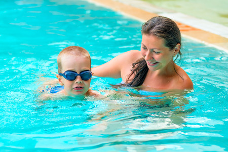 baby 4 5 years: Mom teaches son to swim in the pool Stock Photo