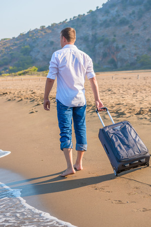 man with a suitcase walking along the beach photo