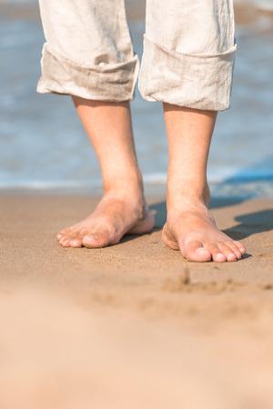 bare feet in the men's linen trousers near the sea