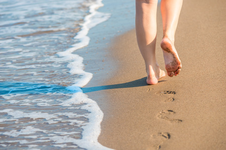 shapely female legs leave footprints on a sandy beach