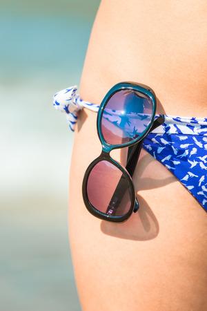 Macro shot of sunglasses on a swimsuit girl